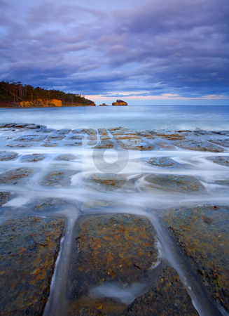 Tessellated Sunset stock photo, A bit of color and light over the odd rock formations known as the tessellated pavement along the Tasman Peninsula. The Tessellated Pavement is an inter-tidal rock platform - a common enough coastal landform. But here an unusual set of geological circumstances have resulted in a rare landform. The flat-lying siltstone was cracked by stresses in the Earth's crust, roughly between 160 million years ago and 60 million years ago. The resulting cracks (joints) are seen as three main sets, one aligned to the north- northeast, a second to the east-northeast and the third to the north-northwest. This jointing, exaggerated by processes of erosion, has created the tiled appearance. When seawater covers the rock platform, fragments of rock are carried away. Near the seaward edge of the platform, sand is the main cause of the erosion. When combined with wave action the erosional process causes loaf or pan formations. by Mike Dawson
