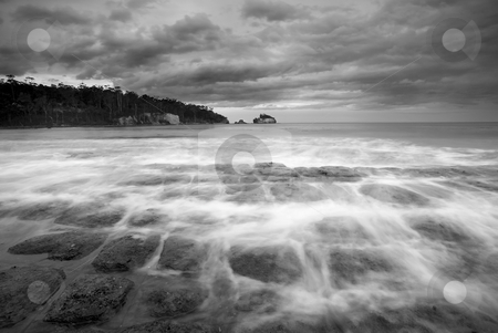Flooding the Cracks stock photo, Rising Tides Flood the cracks of Tesselated PAvement as a storm brews off the coast of the Tasman PEninsula. by Mike Dawson
