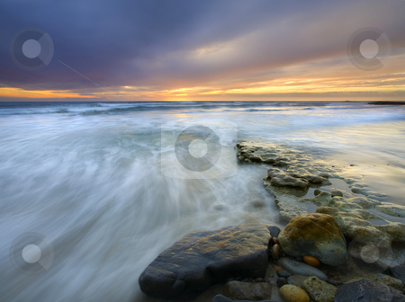 Driven before the storm stock photo, Rolling waves driven onto this rocky shore by a storm looming on the horizon as the sun sets over the coast of California near San Deigo by Mike Dawson