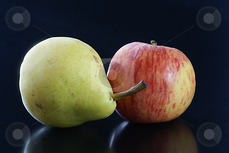 Pear and Apple love stock photo, Close up of a red and yellow apple with a green pear on a black background by Serge VILLA