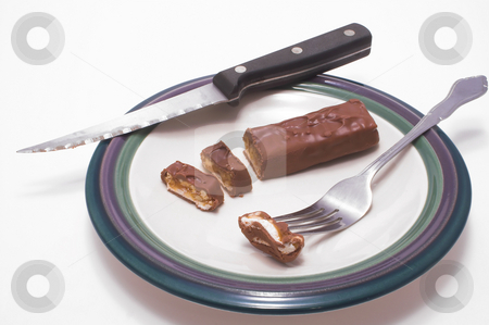 Chocolate Candy Bar stock photo, A chocolate candy bar being sliced in a plate. by Robert Byron