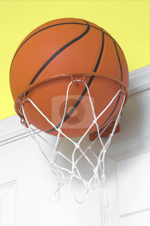 Basketball in Small Hoop stock photo, A basketball in a small indoor basketball goal. by Robert Byron