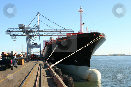 Container ship being loaded stock photo, Dock cranes loading a container ship by Claude Beaubien
