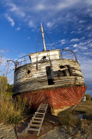 Abandoned shipwreck ashore stock photo, Photo of an abandoned shpireck left ashore, with dark blue sky by Claude Beaubien