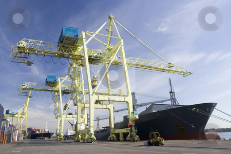Port Cranes unloading a Ship stock photo, Giant container crane unloading a ship in a port by Claude Beaubien