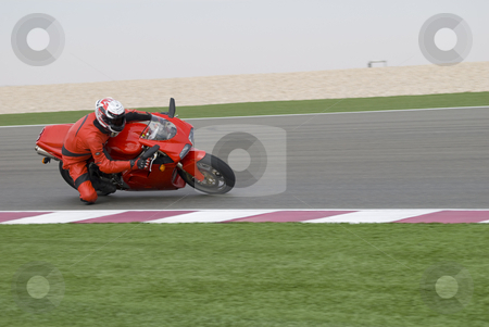 Superbike racing on track stock photo, Superbike rider leaning into a corner at high speed, racing on a race track. by Nicolaas Traut