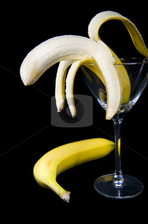 Banana cocktail stock photo, A half peeled banana presented inside a cocktail glass, isolated on a black background.  An unpeeled banana is lying on the side. by Nicolaas Traut