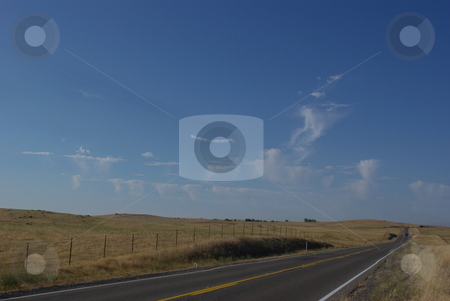 Prairie Road stock photo, A 2 lane road cuts across prairie hills covered with dry grass with unusuale cloud formations in the background. by Lynn Bendickson