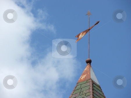 Weathervane Points Direction stock photo, A primitive, old, metal weathervane attached to a lightning rod shows the wind direction on a partly sunny day in northeast Iowa.  Today the weathervane can be a symbol of the search for meaning in life and living. by Dennis Thomsen