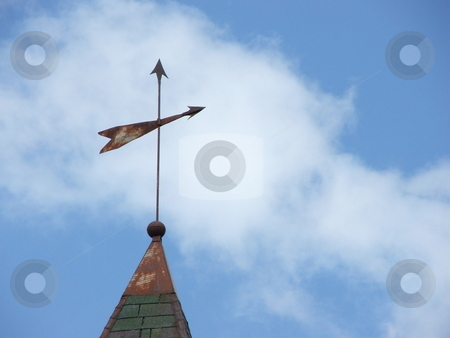 Weathervane Points Direction stock photo, A primitive, old, metal weathervane attached to a lightning rod shows the winds direction on a partly sunny day in northeast Iowa.  Today the weathervane can symbolize the seach for meaning in life and living. by Dennis Thomsen