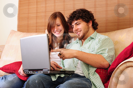 Young couple on computer stock photo, Young couple relaxing on a couch, playing with a laptop computer, laughing and pointing. by Nicolaas Traut
