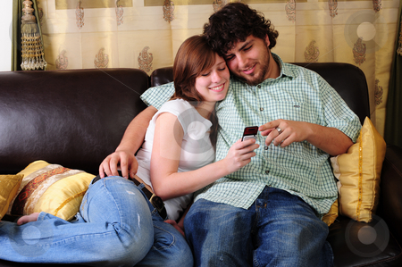 Young couple relaxing on a couch. stock photo, Young couple relaxing on a brown leather couch while looking and pointing at a mobile phone. by Nicolaas Traut