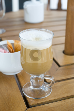 Freshly brewed coffee stock photo, A delicious looking freshly brewed cafe latte served in a glass mug on a wooden table at an outside restaurant. by Nicolaas Traut