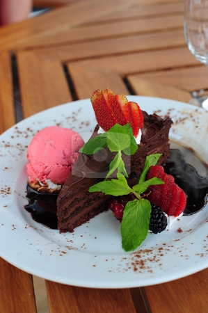 Freshly baked chocolate cake stock photo, Delicious looking freshly baked chocolate cake, presented on a white plate with strawberry ice-cream, berries and mint leaves as garnish. by Nicolaas Traut