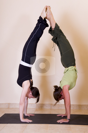 Yoga handstands stock photo, Two beautiful young ladies doing back to back handstands. by Nicolaas Traut