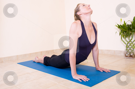 Yoga upward facing dog pose stock photo, A beautiful mature lady in the 'Upward facing dog - Urdhva mukha' yoga position, wearing a black outfit on a blue mat. by Nicolaas Traut