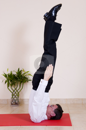 Yoga shoulder stand stock photo, Attractive mature business man dressed in business clothing doing yoga. In this picture doing the 'Shoulder stand - Salamba sarvangasana'. by Nicolaas Traut