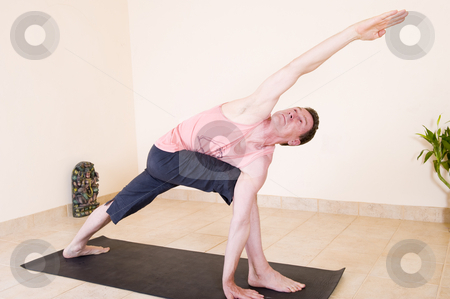 Yoga extended side angle pose stock photo, Attractive mature man in the yoga 'Extended side angle pose - Utthita parsvakonasana. by Nicolaas Traut