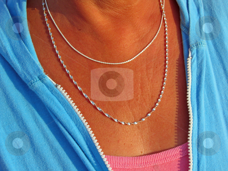 Silver Necklace Duo stock photo, Two silver necklaces adorn the neck of a tanned middle aged woman by Jeff Clow