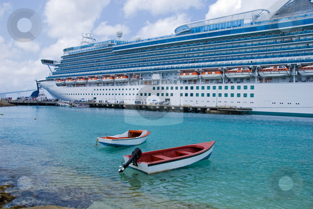 Small Boats and a Big Ship stock photo, Two small boats lie alongside a massive cruise ship in an island harbor by Jeff Clow
