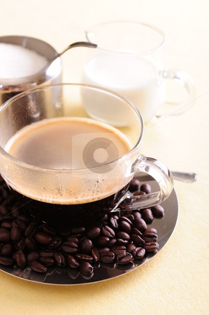 Freshly brewed coffee stock photo, Freshly brewed coffee in a glass cup with coffee beans scattered on the shiny saucer. by Nicolaas Traut