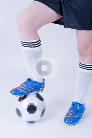 Girl standing with boot on football stock photo, Legs of a girl with football gear standing next to an official UEFA football as used in the Euro Cup, with her boot on the ball. by Nicolaas Traut