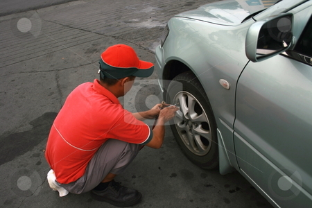 Checking tire pressure stock photo, Station crew providing free tire air checkup by Jonas Marcos San Luis