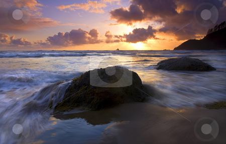Swept Away stock photo, The incoming tide threatens to sweep away the large boulders dotting the sand on Indian Beach as the sun sets over the Tillamook Lighthouse in the distanc. by Mike Dawson