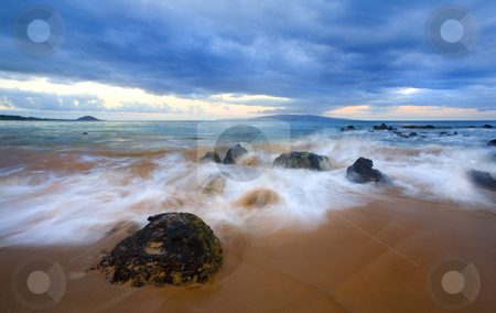 Storm Tides stock photo, The waves of rising tides overcome the lava rock off the coast of Kihei on Maui, Hawauu, Kahaloowe and Molokini are on the horizon under the storm clouds. by Mike Dawson