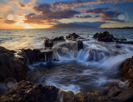 Sunset Cauldron stock photo, A natural cauldron filling as the tides come in at Sunset with the West Maui Mountains in the distance. by Mike Dawson