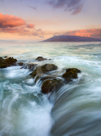 Sunrise Drain stock photo, A colorful sunrise illuminates the clouds over the West Maui Mountains as the tides ebb over a lava rock shelf creating the impression the ocean is draining before my eyes. by Mike Dawson