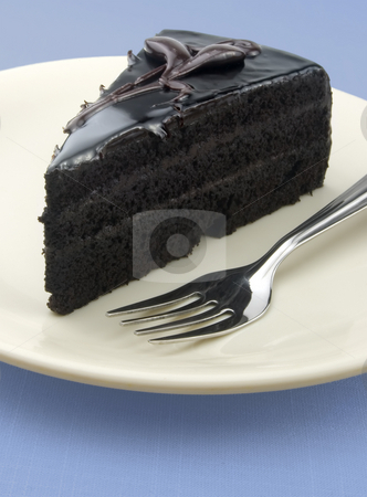 Dark chocolate cake stock photo, Dark chocolate cake with icing on a blue background with fork by Khoj Badami