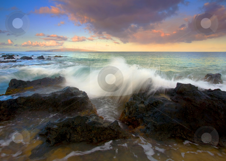 Wave Cresting stock photo, A wave of the incoming tide crests over the lava rocks off the South Shore of Maui as the sun rises and illuminate Kahaloowe in the distance. by Mike Dawson