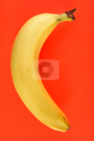 A yellow banana on an orange background. stock photo, A yellow banana on an orange background. by Stephen Rees