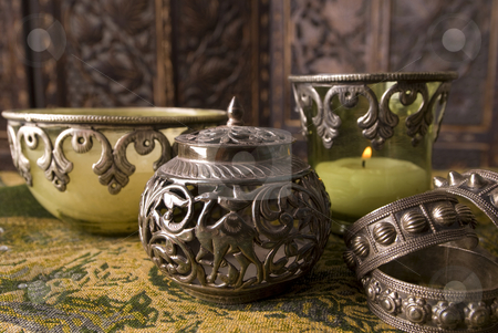 Antique Omani silver stock photo, Antique Omani silver container and serviette holders with candle holders faded out in the background. by Nicolaas Traut