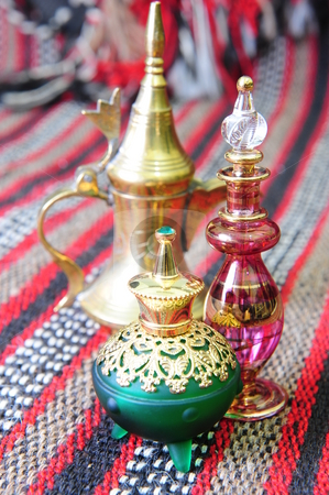 Egyptian perfume bottles stock photo, Egyptian perfume bottles arranged on a hand-woven Omani rug. A copper replica of an old coffee pot is faded in the background. by Nicolaas Traut