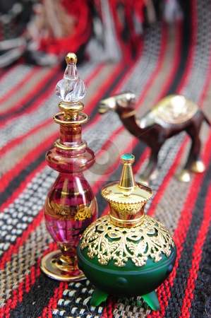 Egyptian perfume bottles stock photo, Egyptian perfume bottles arranged on a hand-woven Omani rug. A small copper replica of a camel is faded in the background. by Nicolaas Traut