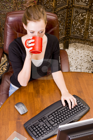 Woman working on PC keyboard and mouse. stock photo, Female executive working on a PC keyboard and/or mouse on a wooden desk. by Nicolaas Traut