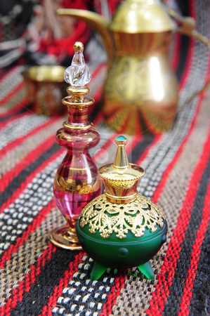 Egyptian perfume bottles stock photo, Egyptian perfume bottles arranged on a hand-woven Omani rug.  A copper replica of a traditional coffee pot and small cup is faded in the background. by Nicolaas Traut