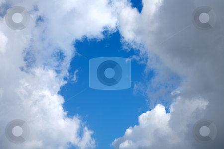 Looking up at a round patch of blue sky surrounded by clouds. stock photo, Looking up at a round patch of blue sky surrounded by clouds. by Stephen Rees