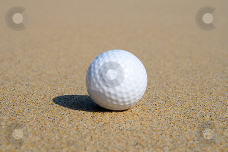 A golf ball in the sand with shallow focus. stock photo, A golf ball in the sand with shallow focus. by Stephen Rees