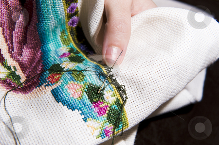 Cross stitch art in the making stock photo, Colorful cross stitch art in the making, showing various color threads and a womans hands working with a needle. by Nicolaas Traut