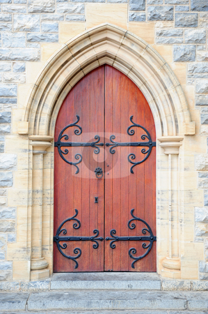 Church door stock photo, Antique church door with black steel decoration in arch on an outside stone wall of a historical church building. by Nicolaas Traut