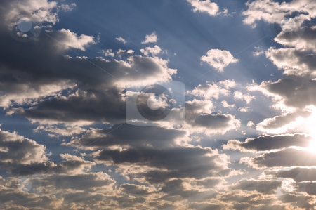 Dramatic clouds in the late afternoon. stock photo, Dramatic late afternoon clouds with the sun on the one edge and rays visible on the blue sky in the background. by Nicolaas Traut