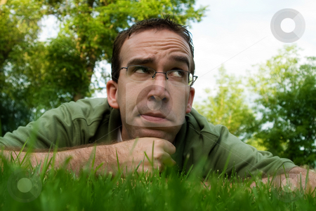 Thinking Man stock photo, A young man lying in the grass and thinking outside by Richard Nelson