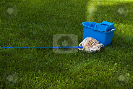 Mop and Pail stock photo, A blue mop and pail sitting in the grass, with steam coming out symbolic of cleaning up the Earth by Richard Nelson