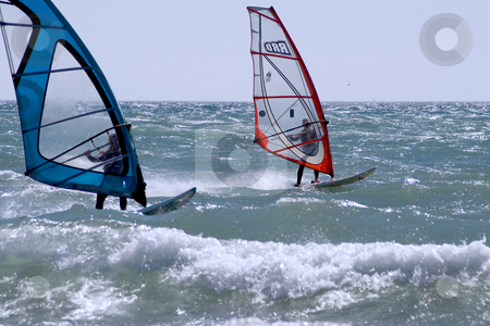 Two Windsurfers stock photo, Two windsurfers in regatta during a windy day in Mediterranean sea. by Serge VILLA