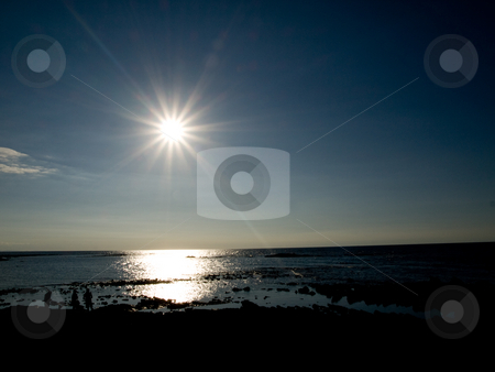 People exploring a beach  stock photo, Group of three people at the beach  against bright sunshine reflecting in the ocean by Laurent Dambies