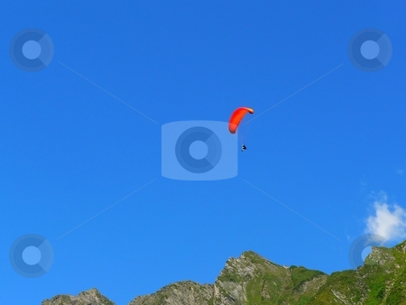 Parachutist above mountains stock photo, Parachutist with orange canopy  over mountain range in Pyrenees by Laurent Dambies