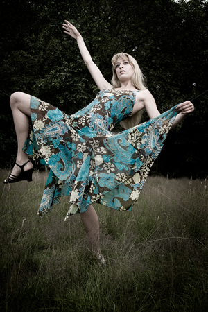 Dancing on the grass stock photo, Young blond woman wearing a dress in the forest by Frenk and Danielle Kaufmann